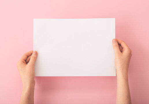 Female hands with blank paper on color background
