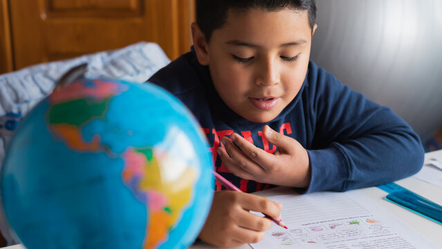 A high angle shot of a Hispanic child studying at home