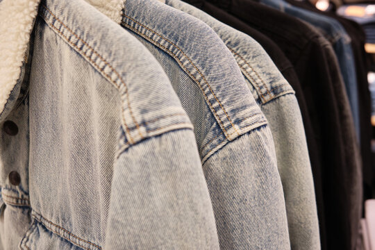 Sherpa jackets on coat hangers. Casual warm denim jackets at retail store