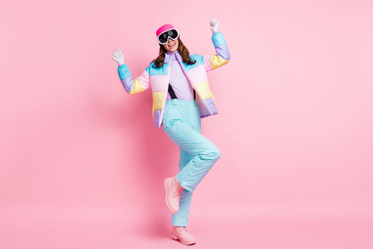 Full length photo of charming lucky woman skier dressed colorful windbreaker rising fists isolated pink color background