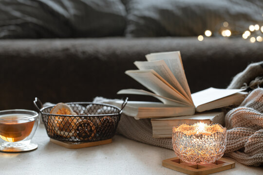Cozy home composition with cup of tea, candlestick and books close up.