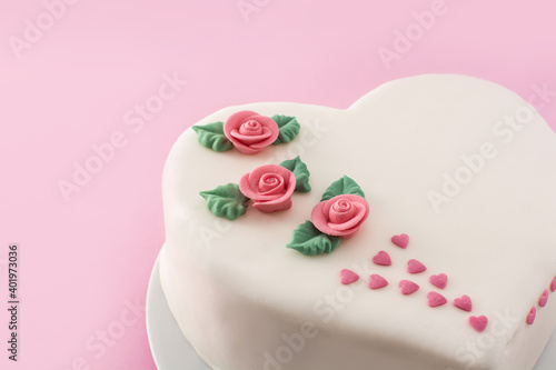 Heart cake for St. Valentine's Day, Mother's Day, or Birthday, decorated with roses and pink sugar hearts on pink background