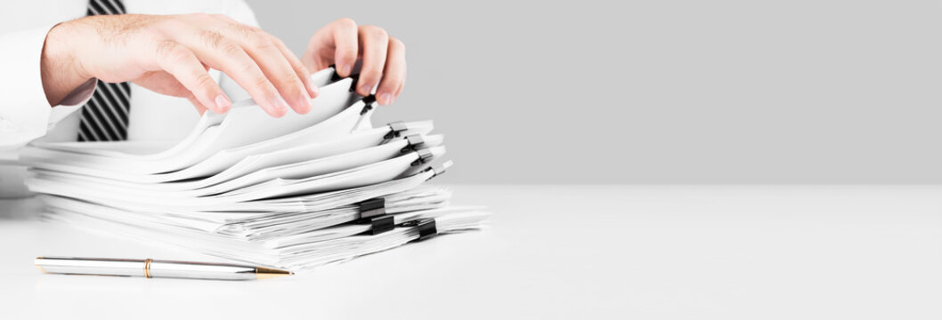 Businessman hands working in stacks of paper files for searching information, business and financial concept.