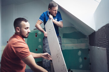 Obraz two professional tilers installing large format tiles. home renovation concept - fototapety do salonu