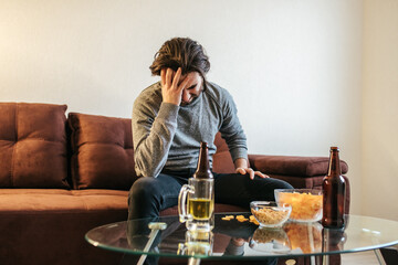 young guy suffering from alcoholism. drunk man suffering from strong headache or migraine sitting on sofa at home. Trying to quit habit. problem of alcohol addiction. Withdrawal pains.