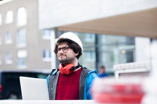 Junger Ingenieur mit Bart und Brille arbeitet auusen mit Helm