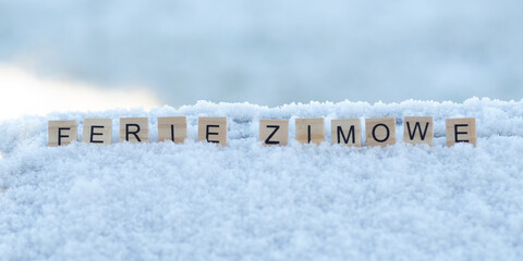 Fototapeta Ferie zimowe - napis z drewnianych kostek, ułożony w śniegu, czas wolny, przerwa zimowa od szkoły, język polski   obraz