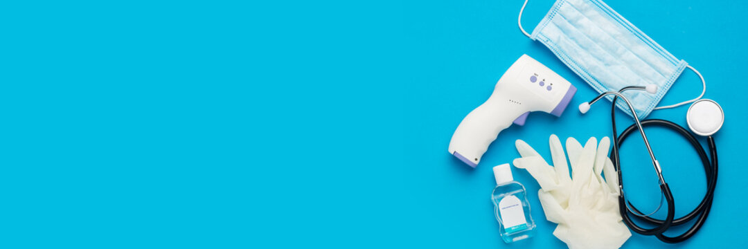 Digital non-contact thermometer, protective mask, latex gloves, medical stethoscope and sanitizer on a blue background. Banner. Top view, flat lay