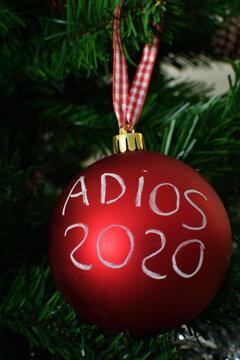 Bola decorativa colgada en un árbol de navidad despidiendo el año 2020.