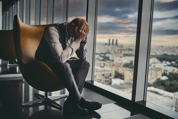 A tired broken man entrepreneur is worrying about the crisis and bankruptcy of the partner company while sitting on an armchair next to the window of a luxurious office skyscraper; a dark sky behind