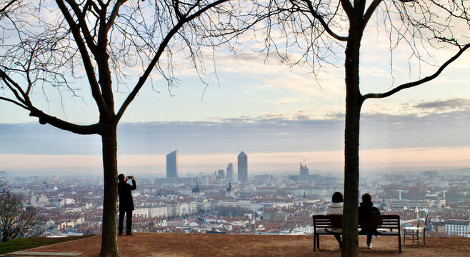 Panoramic picture of 2 people sitting on a bench admiring a wonderful sunrise over the city of Lyon in France and a standing tourist taking pictures