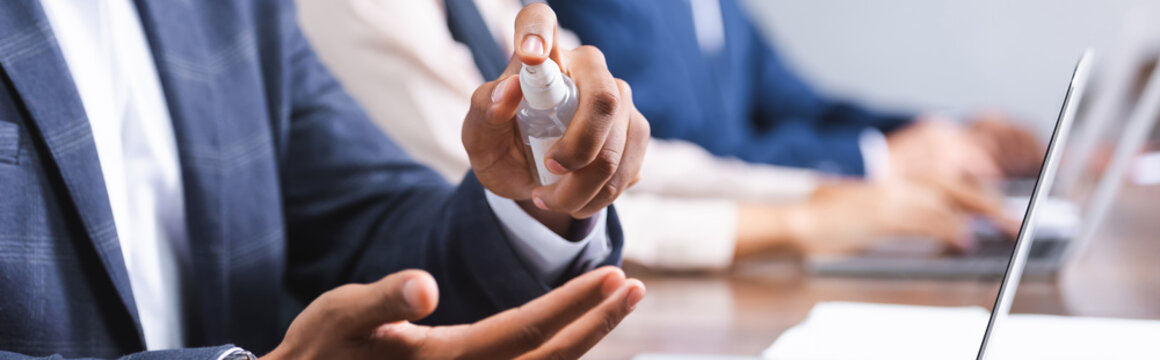 Cropped view of african american businessman applying sanitizer on hands at workplace on blurred background, banner.