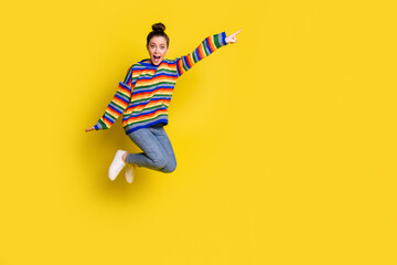 Full size photo of brown bun haired lady jump up point empty space wear jeans rainbow sweater isolated on yellow color background Wall mural