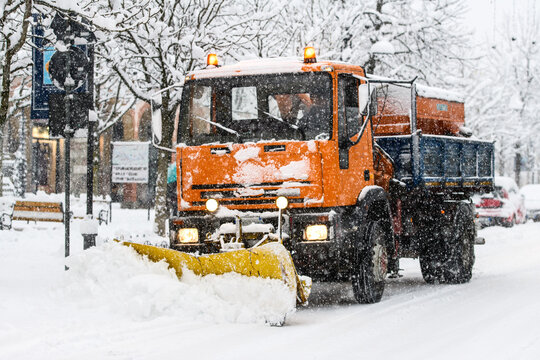 A snow plow at work during snowfall on whitewashed streets in the city