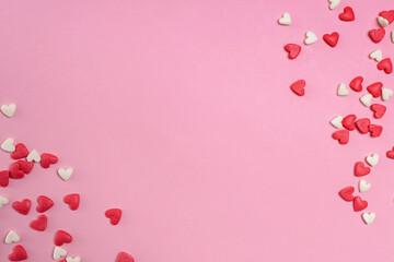 Sugar heart shaped sprinkles on pastel pink background