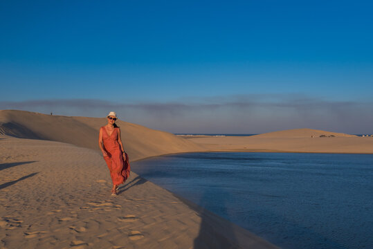 Woman walking in the desert towards the sea