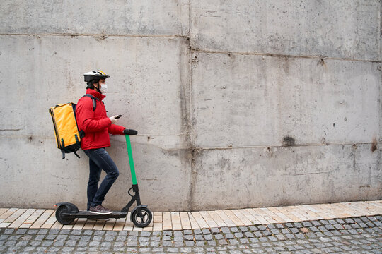 Courier in protective mask walking with bicycle on city street