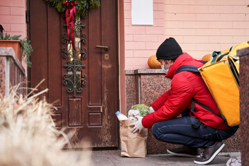 Courier putting paper bag with food near entrance