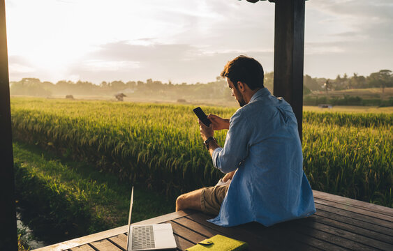 Anonymous guy messaging on smartphone during sunset in countryside