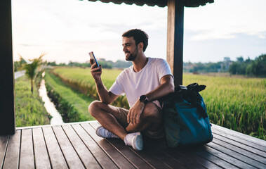 Cheerful male traveler using cellphone in tropical countryside