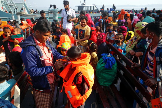 Rohingya man helps a boy to wear a life jacket after getting on board of a navy vessel that will carry them to Bhasan Char island, in Chattogram