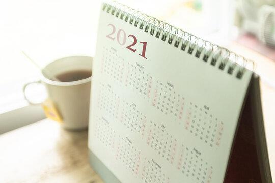 Paper desktop calendar 2021 schedule with tea cup on wooden desk