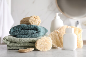Wall Mural - Natural loofah sponges, towels and cosmetic products on table in bathroom