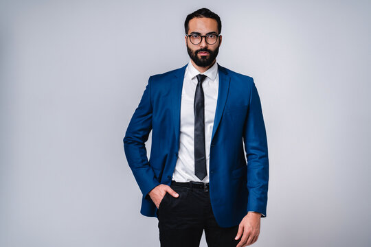 Successful young Arab businessman in formal attire isolated over grey background