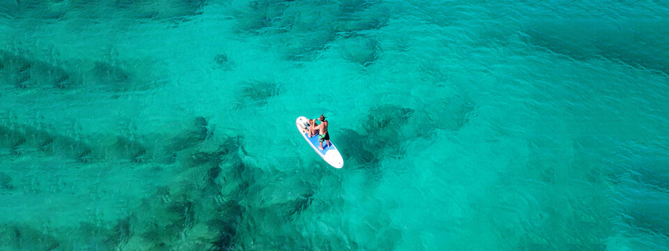 Aerial drone ultra wide photo of couple practice SUP or Stand Up Paddle board in tropical exotic bay with turquoise sea