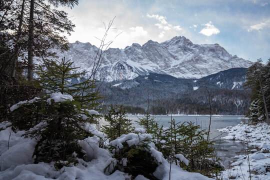 """The lake """"Eibsee"""" in winter with the """"Zugspitze"""" (The highest mountain of Germany ) in  the background. Trees in the foreground"""