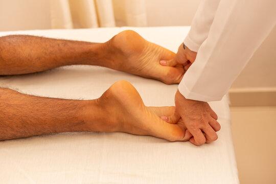 Close em mãos de massoterapeuta aplicando massagem em pé de paciente.