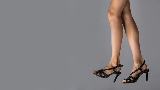 Sexy female legs in black shoes isolated over grey background