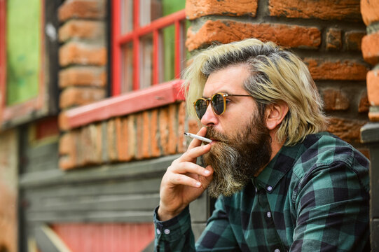 brutal caucasian male in glasses. Man Smoking Outdoor. Fashionable mature man smoking cigarette. Punk hipster man smoking. Smoking and habit. secondhand or passive smoke. copy space
