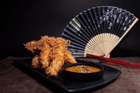 Camarones fritos con salsa de mango decorados con un abanico estilo japonés