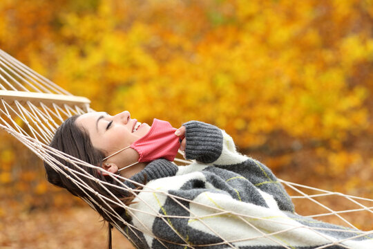 Happy woman taking off mask breathing fresh air on hammock