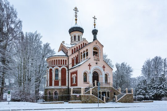 Marianske Lazne, Czech Republic - December 29 2020: Winter view of the orthodox russian church of St Vladimir with red facade surrounded by trees covered with white snow. Grey sky in the background.