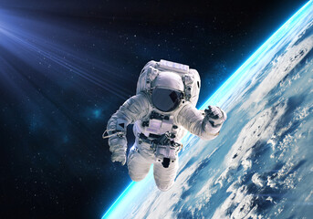 Science fiction walpaper of a lonely astronaut in free spacewalk orbit Earth planet globe with glow and nebulae on the background. Elements of this image furnished by NASA