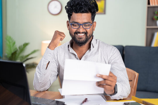 Young man reading paper letter feeling overjoyed by good news clenched fist - Concept of new Job offer or promotion, college admission and loan approvel.
