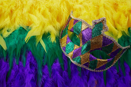 Mardi gras carnival concept with face mask and Mardi gras colors feathers.