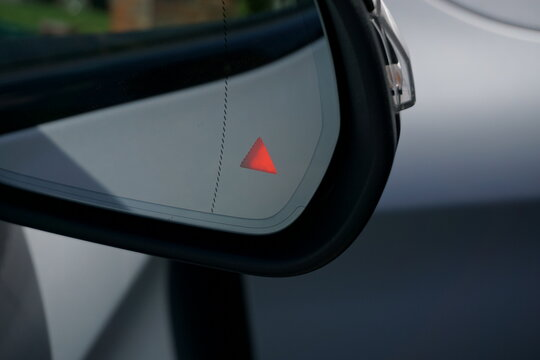 Close up of illuminated blind spot monitor warning on door mirror of modern luxury car.