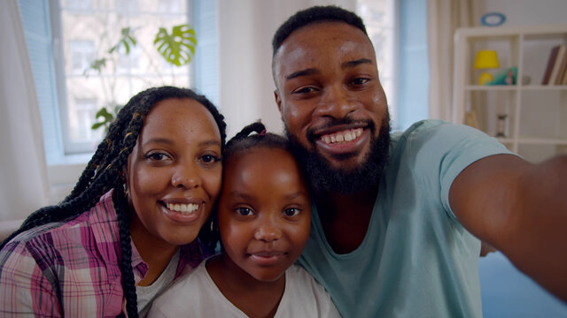 Young smiling african parents with cute daughter having video conference at home