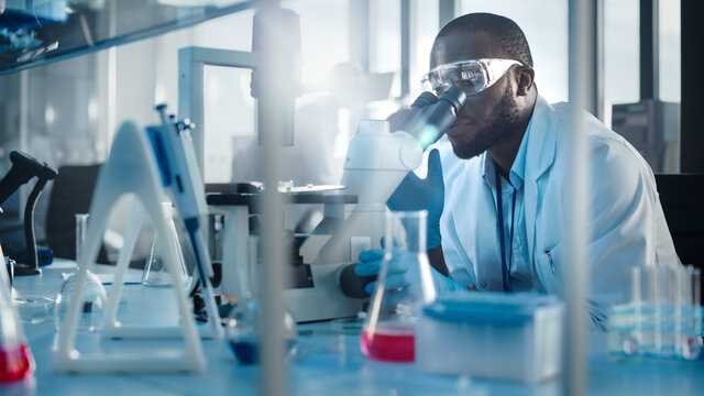 Medical Development Laboratory: Black Male Scientist Looking Under Microscope, Inspecting Petri Dish. Professionals Working in Advanced Scientific Lab doing Medicine, Vaccine, Biotechnology Research