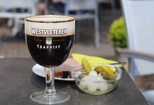 WESTVLETEREN, BELGIUM – MAY 5 2014: famous and limited available strong dark trappist served in appropriate glass in the café next to the abbey where it is brewed. Best beer of the world several times