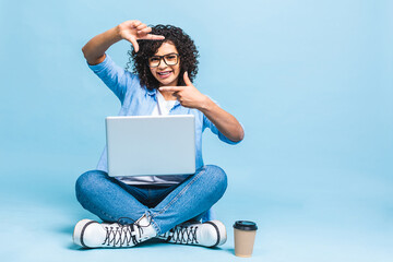 Portrait of african american black woman in casual sitting on floor in lotus pose and holding laptop isolated over blue background