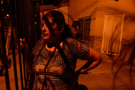 Rosalia Reyes, 47, who was sentenced to eight years in prison after her baby died during a home childbirth, looks through the fence of her home where she will serve the rest of her time under house arrest, in Zarate