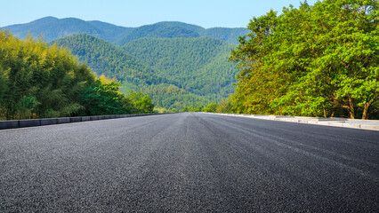 Asphalt road and green mountain under blue sky.Road and mountain background.