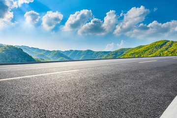 Asphalt road and green mountain under blue sky.Road and mountain background. Fotomurales