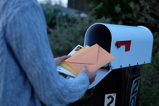 woman collect mails from a mailbox