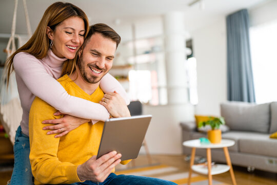 Young couple in love at home websurfing on internet