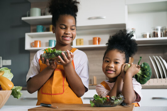Happy sister black skin with salad on plate in kitchen